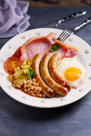 Full English or Irish breakfast with sausages, bacon, egg, tomatoes, fries and beans. Nutritious and healthy morning meal