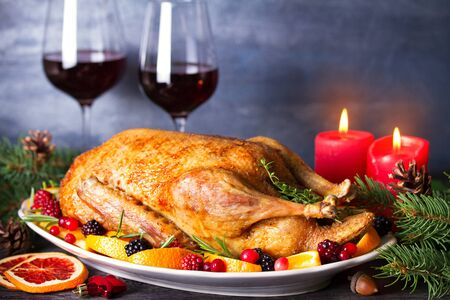 Whole roasted duck with oranges, berries and herbs, glasses of red wine. Christmas decorations. Dish for Christmas Eve. Copy space