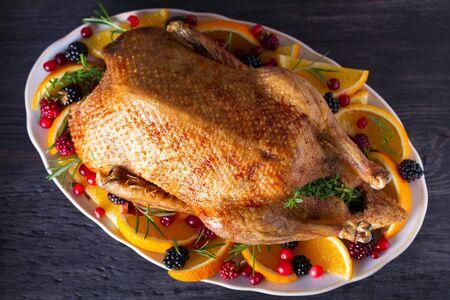 Ganze gebratene Ente mit Orangen, Beeren und Kräutern. Ansicht von oben, Ansicht von oben Standard-Bild