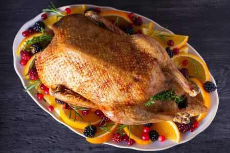 Whole roasted duck with oranges, berries and herbs. View from above, top view