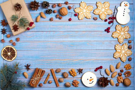 Christmas gingerbread cookies and decorations on blue wooden background with room for text. Winter holidays concept, flat lay