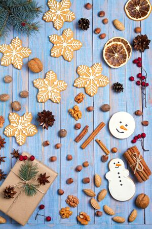 Christmas gingerbread cookies and decorations on blue wooden background. Winter holidays concept, flat lay