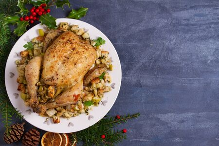 Roasted chicken with apple and bread stuffing. Christmas decorations. Dish for Christmas Eve. New Year food menu. Layout, flat lay, view from above, copy space 写真素材