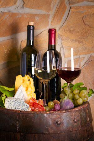 Wein mit Käse, Schinken und Früchten neben altem Fass im Weinkeller. Weinverkostungskonzept