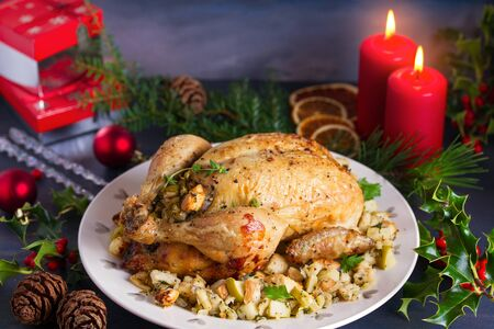Roasted chicken with apple and bread stuffing. Christmas decorations. Dish for Christmas Eve. New Year food menu.