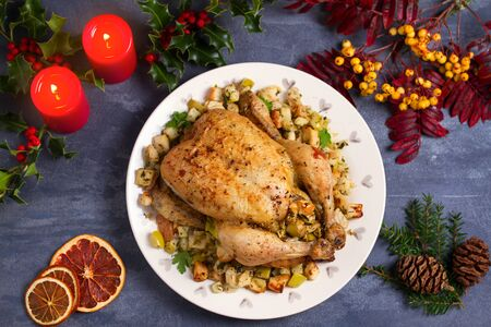 Roasted chicken with apple and bread stuffing. Christmas decorations. Dish for Christmas Eve. New Year food menu. Flat lay, view from above