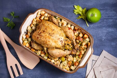 Roasted chicken with apple and bread stuffing in baking dish. View from above, top