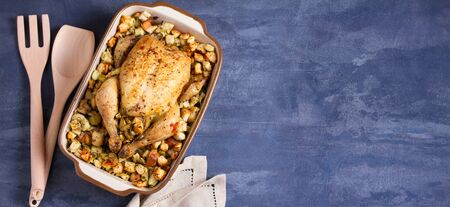 Roasted chicken with apple and bread stuffing in baking dish, copy space