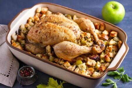 Roasted chicken with apple and bread stuffing in baking dish 写真素材