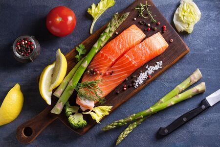 Fresh raw salmon fish fillet, asparagus, lemon, herbs and spices. View from above, top