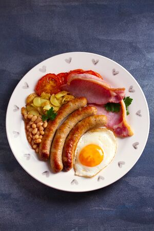 Sausages, bacon, egg, tomatoes, fries and beans on white plate. Overhead vertical image Stock Photo