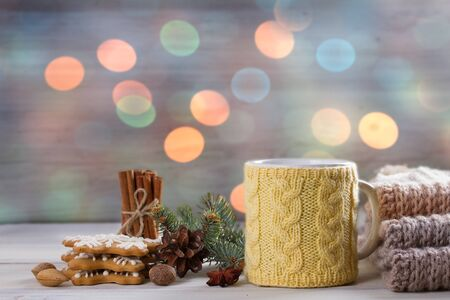 Cup of hot drink. Mug in knitted mitten. Christmas lights at background. Holiday Christmas concept, room for text