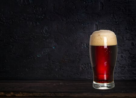 Glass of beer on wood dark background with copyspace for text