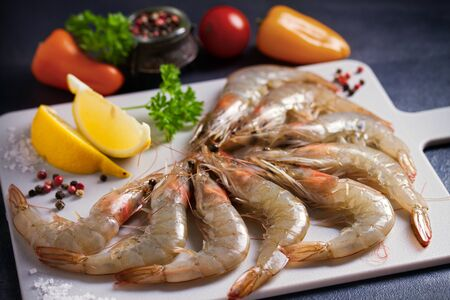 Fresh raw prawn shrimps with ingredients for cooking on chopping board. Seafood Stock Photo