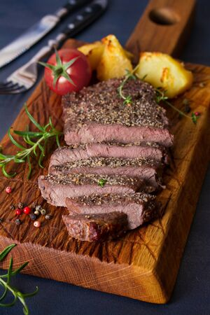 Grilled fillet beef steak with potatoes on serving board Stock Photo