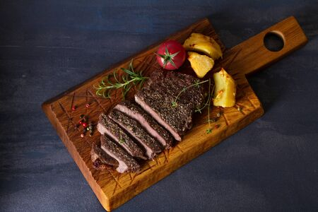 Grilled fillet beef steak with potatoes on serving board. View from above, top view