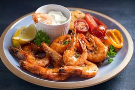 Shrimps or prawns with vegetables, garlic and sauce on plate  Stock Photo