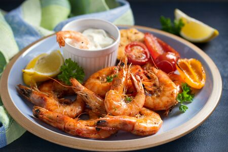 Shrimps or prawns with vegetables, garlic and sauce on plate 写真素材 - 137830869