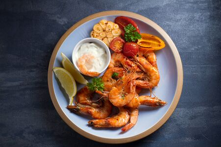 Shrimps or prawns with vegetables, garlic and sauce on plate. Overhead, top view