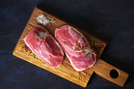 Raw fresh meat, duck breast fillet on wood chopping board with rosemary and seasons. Flat lay Stock Photo