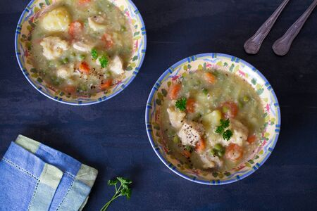 Bowl of chicken stew with vegetables on dark gray background.