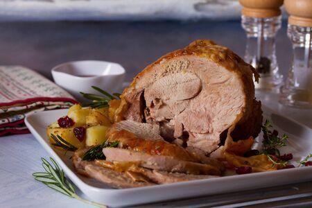Roast turkey leg with potatoes, cranberries and rosemary on white plate. horizontal image