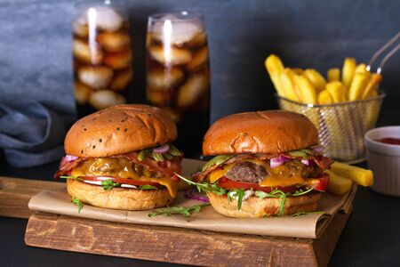 Beef burgers and french fries on serving board. Street food, fast food Imagens