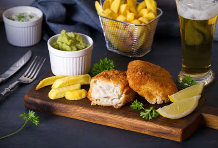 Battered fish with french fries, mushy peas and sauce. Fish and chips, glass of beer. Horizontal image Banco de Imagens