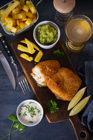 Battered fish with french fries, mushy peas and sauce. Fish and chips. Overhead horizontal image Banco de Imagens