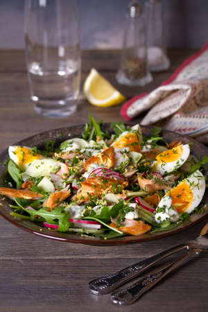 Smocked mackerel fish salad with eggs, arugula and vegetables. vertical photo