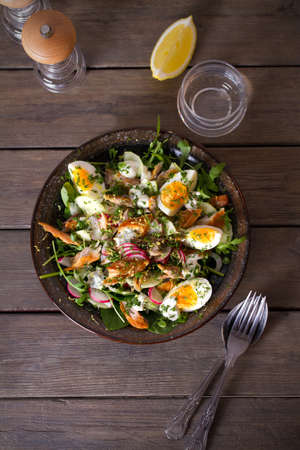 Smocked mackerel fish salad with eggs, arugula and vegetables. Overhead vertical photo 免版税图像