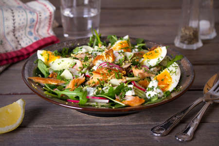 Smocked mackerel fish salad with eggs, arugula and vegetables. horizontal photo