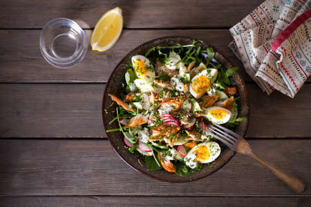 Smocked mackerel fish salad with eggs, arugula and vegetables. Overhead horizontal photo 免版税图像