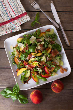 Peach and cured ham salad with cheese, basil, arugula and cucumbers. View from above, top studio shot