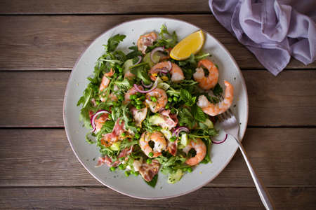 Shrimp salad with bacon, cucumber and radish on wooden background close up. Clean eating. Flat lay, overhead