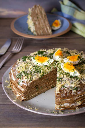 Layered liver cake with cheese, mayonnaise and dill. Savory cake. vertical photo