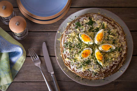 Layered liver cake with cheese, mayonnaise and dill. Savory cake. Overhead horizontal photo