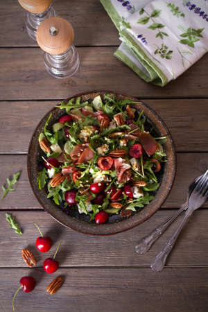 Strawberry and prosciutto salad with gorgonzola cheese and arugula. Healthy food. Overhead vertical photo