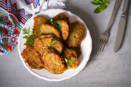 Potato cakes. Vegetable fritters, pancakes, latkes - dish consisting of pan fried shredded potatoes. View from above, top view