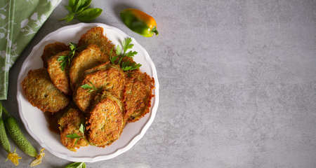 Potato cakes. Vegetable fritters, pancakes, latkes - dish consisting of pan fried shredded potatoes. View from above, top view, copy space
