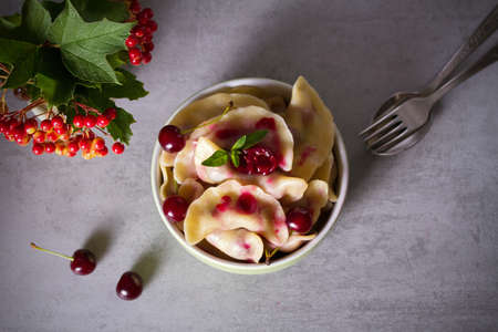 Dumplings, filled with cherries. Varenyky, vareniki, pierogi, pyrohy - popular dish in many countries. Overhead horizontal photo