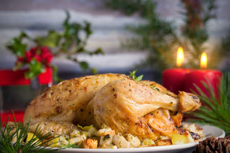 Roasted chicken stuffed with apple bread and celery. Christmas thanksgiving dinner table