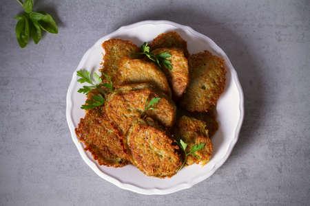 Potato cakes. Vegetable fritters, pancakes, latkes on white plate. Overhead flatlay photo