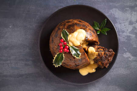 Richly spiced Christmas pudding cake with custard and Christmas decorations. Overhead, flat lay photo