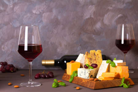 Glasses and bottle of red wine with cheese and nuts. Copy space Stock Photo