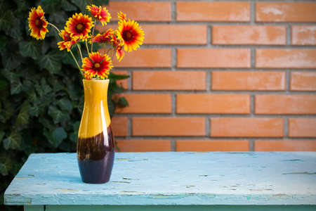 Flower bouquet in vase in front of stone wall. Outdoor arrangement of flowers. View with copy space 免版税图像