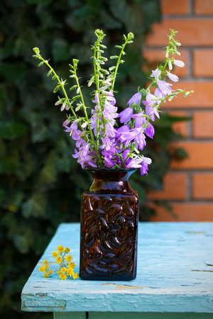 Flower bouquet in vase in front of stone wall. Outdoor arrangement of flowers 免版税图像