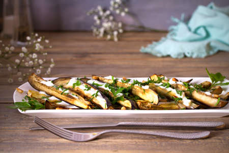 Eggplants or aubergines with yoghurt sauce, nuts and parsley. Horizontal photo