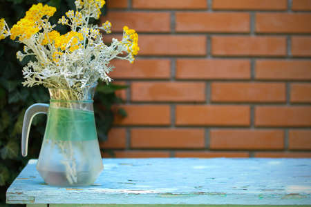 Flower bouquet in front of stone wall. Outdoor arrangement of flowers. Herbs in vase. View with copy space Reklamní fotografie - 164106000