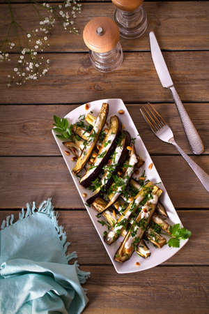 Eggplants or aubergines with yoghurt sauce, nuts and parsley. Vertical overhead photo